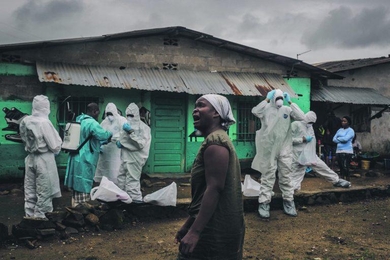 Sugulane leinab Punase Risti matmismeeskonna juures, mis valmistub ära viima Ofori Gweah' surnukeha. Gweah suri ebolasse Monrovias Libeerias.